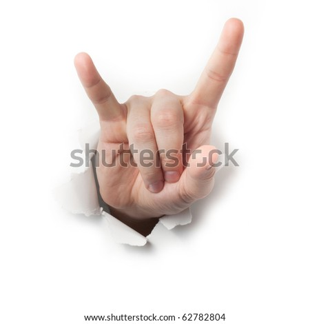 Hand making the heavy metal or satan gesture breaking through a thin wall or paper