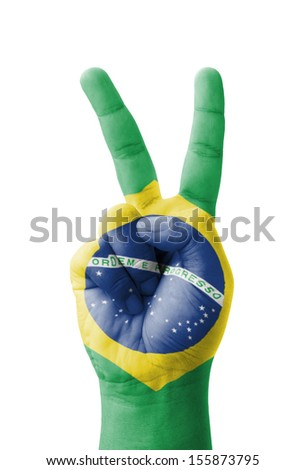 Hand making the V sign, Brazil flag painted as symbol of victory, win, success - isolated on white background - stock photo