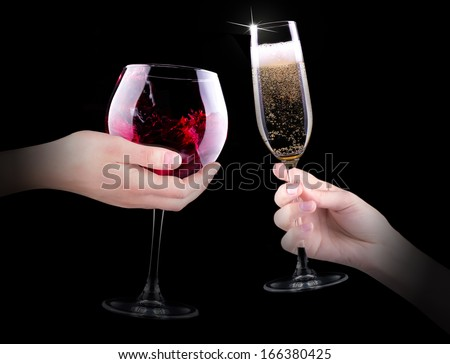hand making toast with glass of red splashing wine and champagne on black background - stock photo