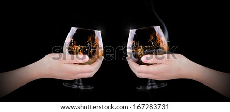 hand making toast with glass splashing Cognac or brandy on black background - stock photo