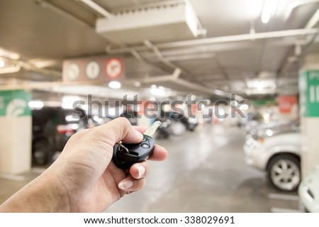 Hand male Asian ,holding car remote on Blurred image parking in the mall, bokeh background  - stock photo