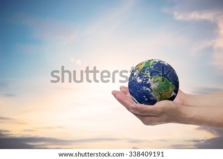 hand male gesture holding the world over blur sky in twilight hours background:human hands with safe world:conservation environment conceptual:clean ecosystem.Elements of this image furnished by NASA - stock photo