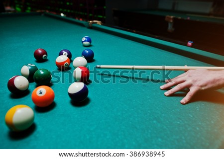 Hand man holding billiard cue to shoot balls - stock photo