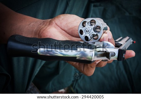 hand man holding show gun emptied storage cylinder of revolver handgun - stock photo