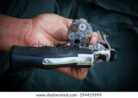hand man holding show gun  storage cylinder .357 magmun of revolver handgun - stock photo