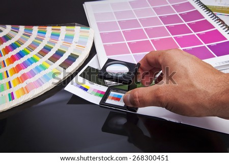 Hand man with black glass standing on a leaf of the test print and pantone - stock photo