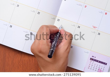 Hand marked the important date on the daily planner  - stock photo