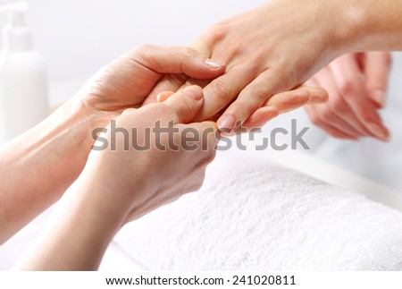 Hand massage, a woman in the beauty salon.Treatment hand and nail care, the woman to a beautician for a manicure.