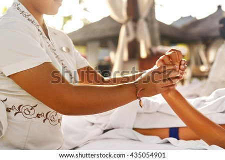Hand Massage At Day Spa Salon Outdoors. Closeup Of Masseur Hands Massaging Relaxed Female Hand With Aromatherapy Oil. Young Woman Relaxing At Beauty Centre. Body Health, Skin Care Treatment Concept - stock photo