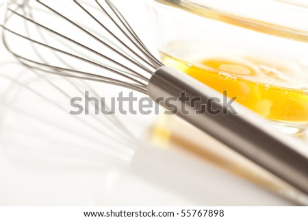 Hand Mixer with Eggs in a Glass Bowl on a Reflective White Background. - stock photo