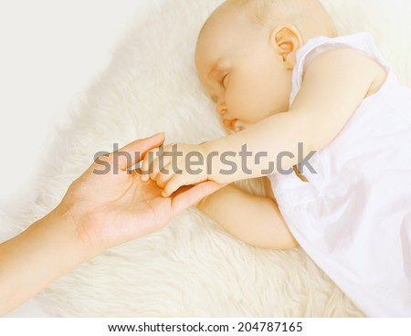 Hand mother and sleep baby