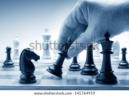 Hand moving a chess piece on board - stock photo
