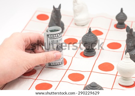 Hand moving US hundreds banknote or bills on chessboard for financial background