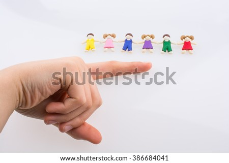 Hand near colorful dressed children figures on a white background