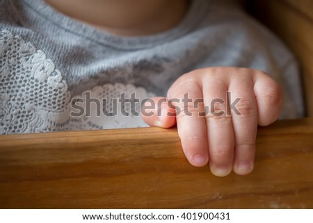 Hand of a baby girl holding onto the side of her chair - stock photo