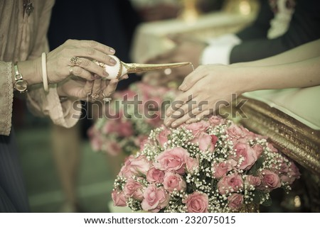 hand of a bride and groom receiving holy water from elders in thai culture wedding ceremony  - stock photo
