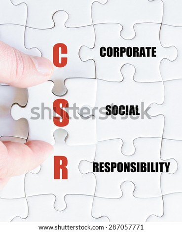 Hand of a business man completing the puzzle with the last missing piece.Concept image of Business Acronym CSR as Corporate Social Responsibility - stock photo