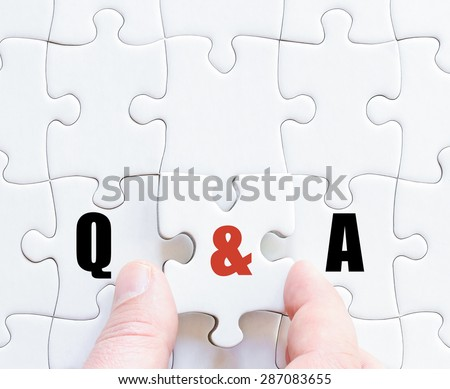 Hand of a business man completing the puzzle with the last missing piece.Concept image of Business Acronym Q&A as Questions and Answers