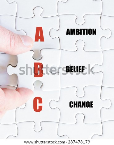 Hand of a business man completing the puzzle with the last missing piece.Concept image of Business Acronym ABC as Ambition Belief Change - stock photo