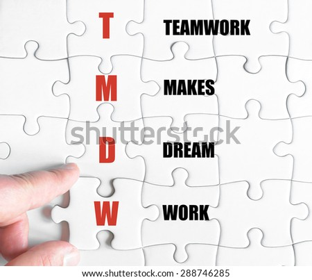 Hand of a business man completing the puzzle with the last missing piece.Concept image of Business Acronym TMDW as TeamWork Makes Dream Work - stock photo