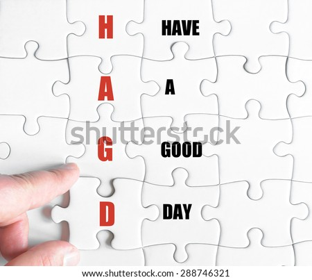 Hand of a business man completing the puzzle with the last missing piece.Concept image of Business Acronym HAGD as Have A Good Day