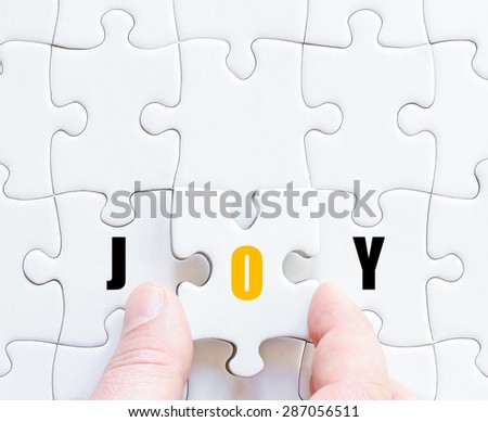 Hand of a business man completing the puzzle with the last missing piece.Concept image of puzzle board with motivational word JOY