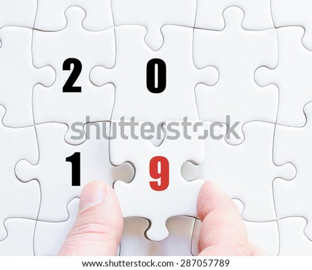 Hand of a business man completing the puzzle with the last missing piece. Concept image of puzzle board with year 2019