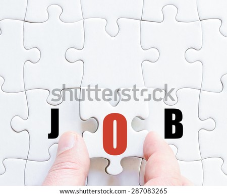 Hand of a business man completing the puzzle with the last missing piece.Concept image of puzzle board with motivational word JOB