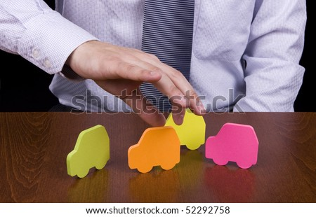Hand of a business man picking the orange car - stock photo