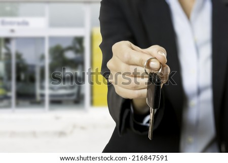 hand of a business woman offering a car key. Car dealer background - focus on the fingers