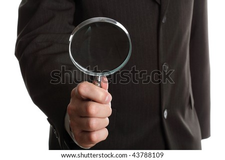 Hand of a businessman holding a magnifying glass on white background - stock photo