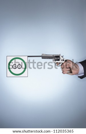 Hand of a businessman holding pistol with go flag - stock photo