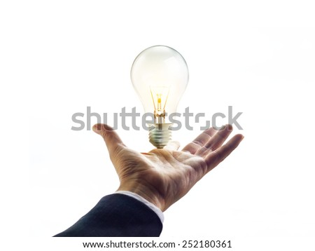 Hand of a businessman reaching towards light bulb, business concept