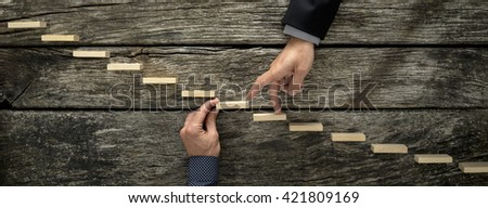 Hand of a businessman supporting a wooden step for his colleague to walk his fingers up towards success, conceptual of business teamwork and collaboration. - stock photo