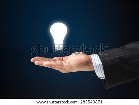 Hand of a businessman with a floating bulb.  Concept image for idea, creativity, genius - stock photo