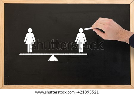 Hand of a businessman writing with a white chalk against blackboard with copy space - stock photo