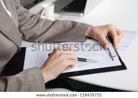 Hand of a businesswoman at her desk with a pen and a clipboard - stock photo