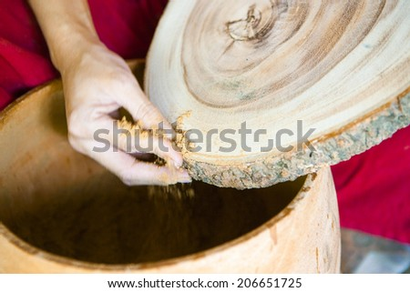 hand of a carpenter repairing a cross section of wood - stock photo