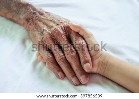 hand of a child and old man on white table cloth on a white bed in a hospital. - stock photo