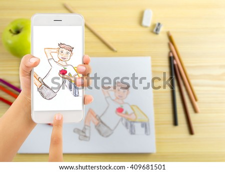 hand of a child holding and using a modern smartphone and making a photo to a picture to send to their parents for mother day and father - stock photo