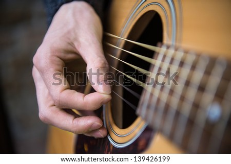 Hand of a country guitarist playing acoustic guitar - stock photo