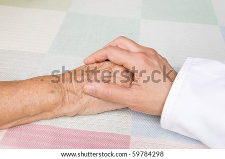 hand of a doctor holding the hand of an elderly patient - stock photo
