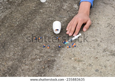 Hand of a drug addict near a syringe and pills. Simulate a suicide - stock photo