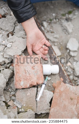 Hand of a drug addict reaching for a syringe and pills. Simulated