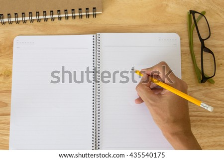 hand of a man hold the pencil and writing something on blank page - stock photo