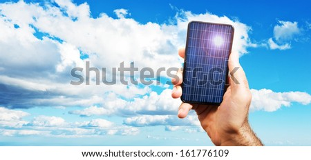 hand of a man holding a photovoltaic cell exposed to the sun. on a background of a blue sky with white clouds of varied - stock photo