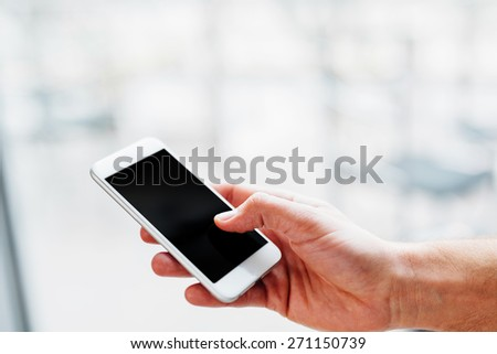 Hand of a man holding a smartphone and touching the screen - stock photo