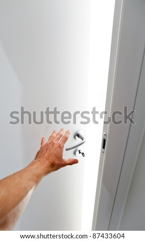 Hand of a man open white door from the dark into the room full of light - stock photo