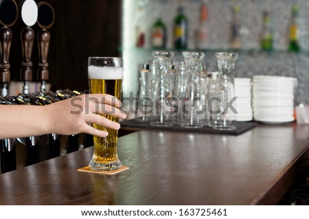 Hand of a man reaching for a pint of beer in a pub which is standing on a wooden bar counter - stock photo
