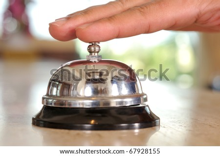 Hand of a man using a hotel bell - a series of HOTEL images. - stock photo
